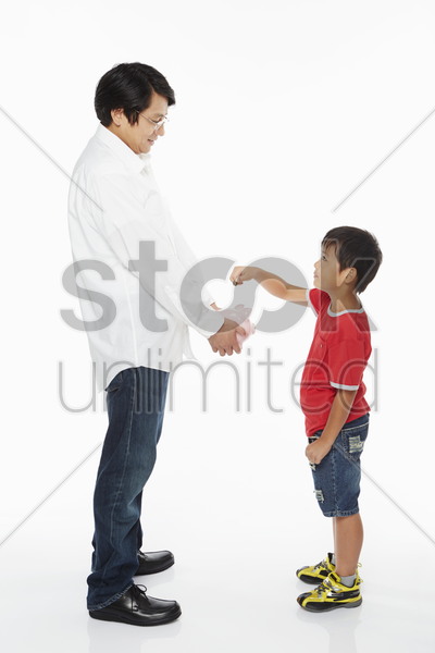 boy putting money into a piggy bank stock photo