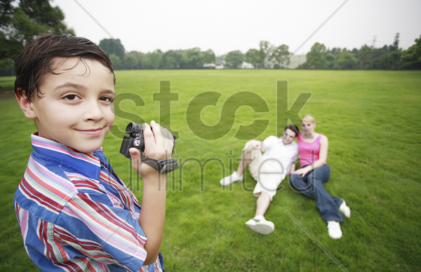 boy recording images of young couple stock photo