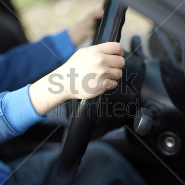 boy's hands on the steering wheel stock photo