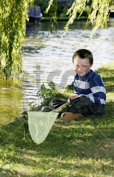 boy sitting by the river holding fishing net stock photo