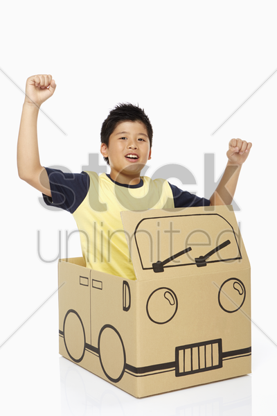 boy sitting in a cardboard bus, cheering stock photo