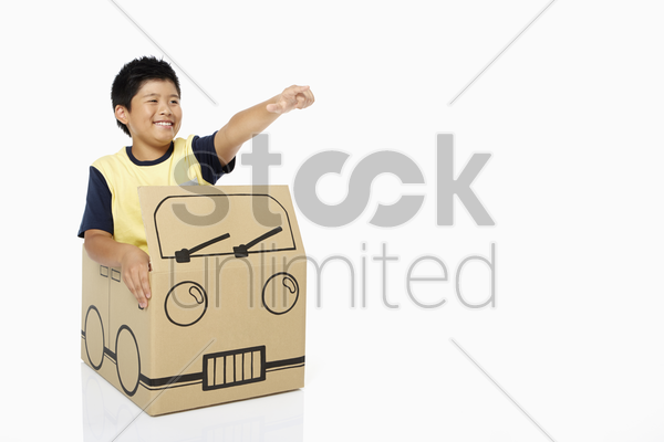 boy sitting in a cardboard bus, pointing stock photo