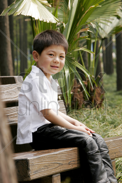 boy sitting on the bench smiling stock photo