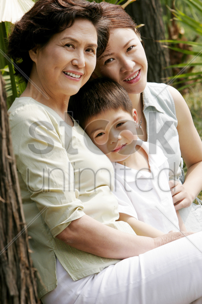 boy sitting on the bench with his mother and grandmother stock photo