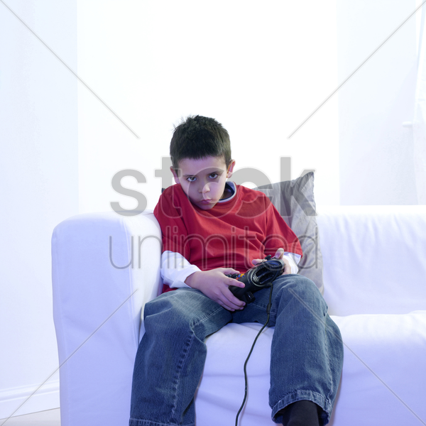 boy sitting on the couch playing with video game console stock photo