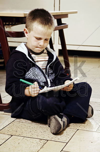 boy sitting on the floor drawing stock photo