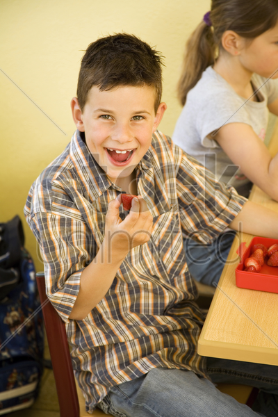 boy smiling at the camera while holding a strawberry stock photo