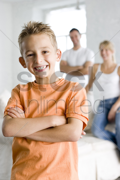 boy smiling at the camera with his parents in the background stock photo