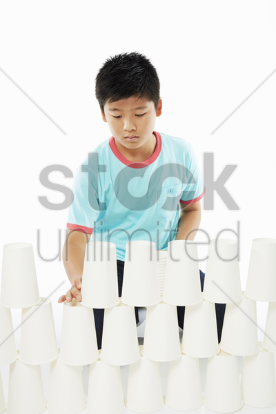 boy stacking up disposable cups and concentrating stock photo