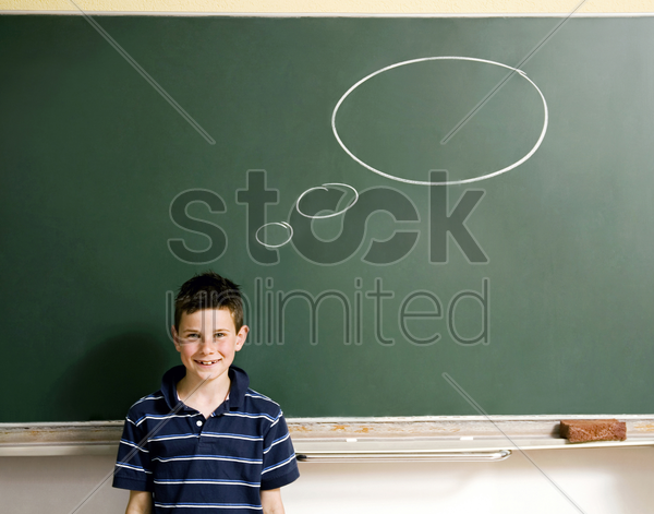 boy standing in front of a blackboard with thought bubble stock photo
