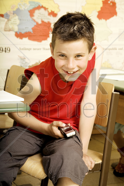 boy text messaging on the mobile phone while sitting in the classroom stock photo