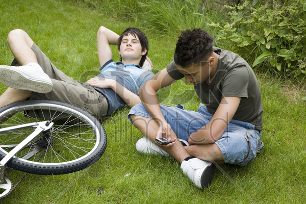 boy text messaging on the phone, another boy resting on the grass stock photo