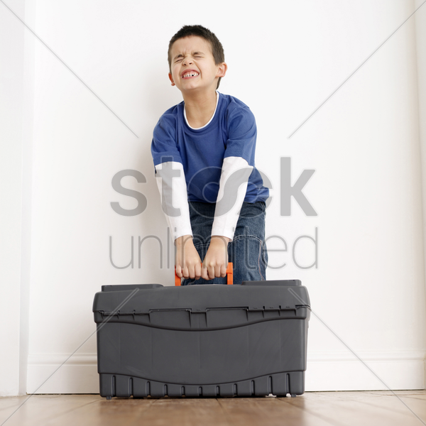 boy trying to carry up a toolbox stock photo