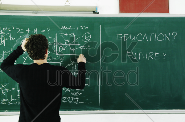 boy trying to solve the equation on the blackboard stock photo