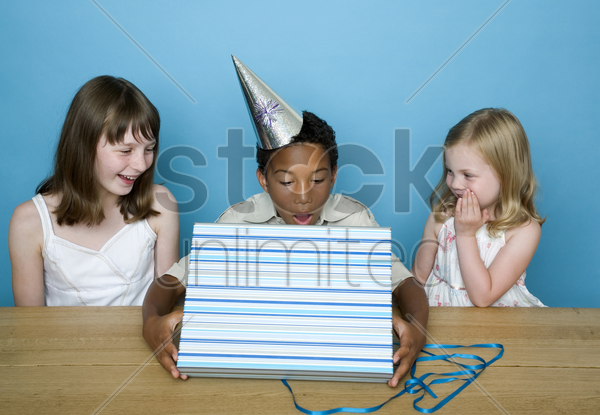 boy unwrapping his present stock photo