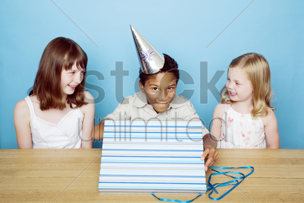 boy unwrapping present with his friends looking stock photo