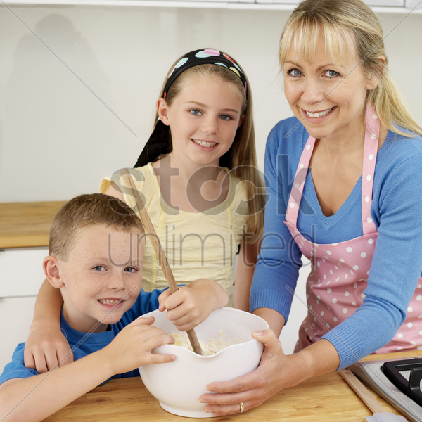 boy using wooden ladle, woman and girl smiling at camera stock photo