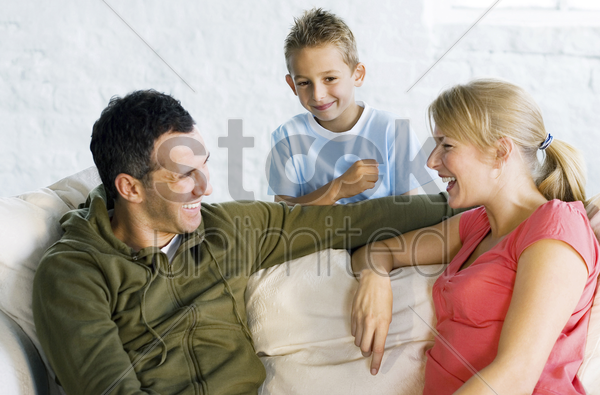 boy watching parents sitting on the couch talking stock photo