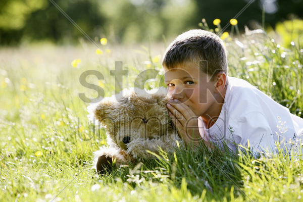 boy whispering into teddy bear's ear stock photo