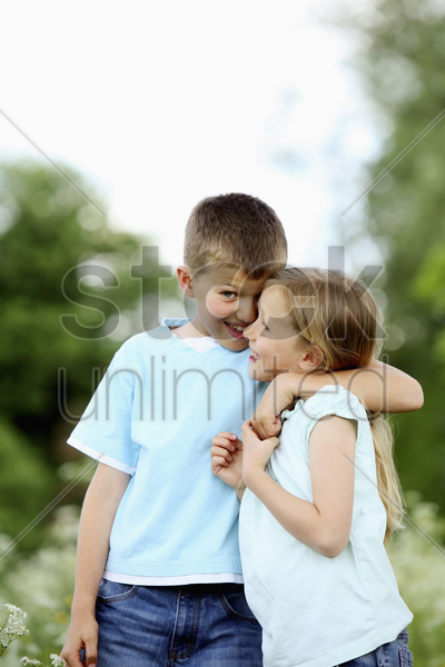 boy with arm around girl's shoulders stock photo