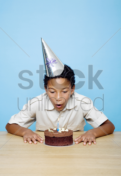 boy with party hat blowing the candle on his birthday cake stock photo