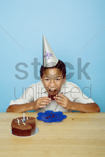 boy with party hat eating cake stock photo