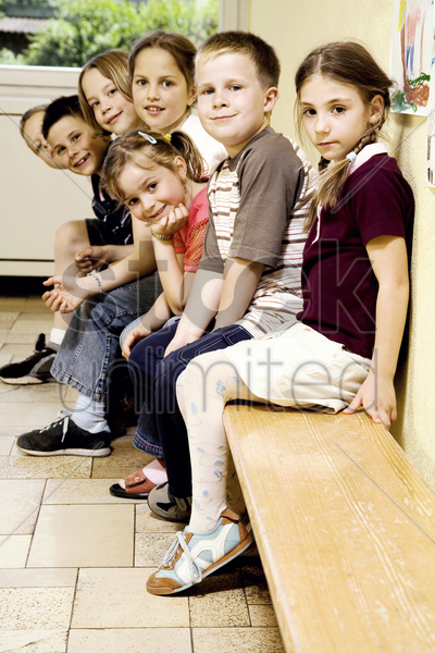 boys and girls sitting on the bench stock photo