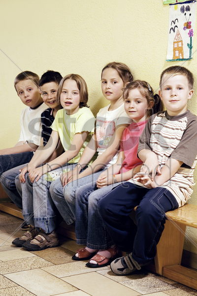 boys and girls sitting together on a bench stock photo