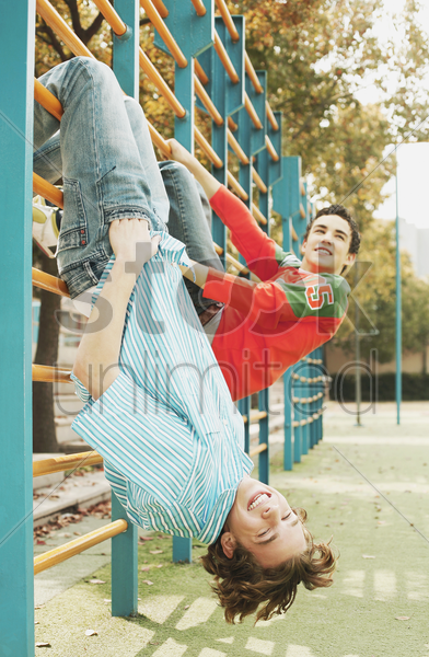 boys hanging on gymnastic bars stock photo