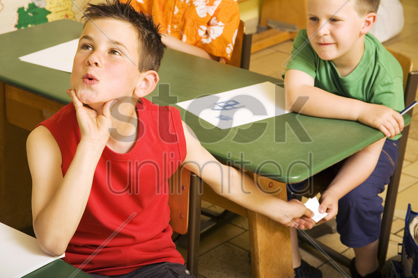boys passing note under the table stock photo