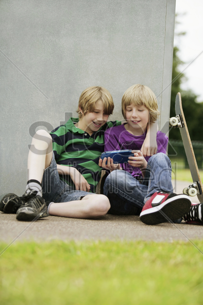 boys playing handheld video game together stock photo