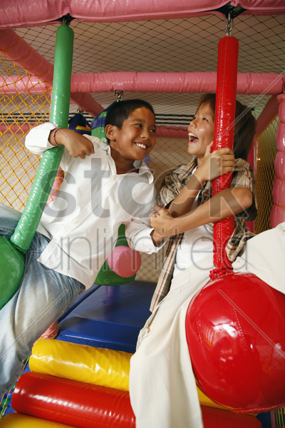 boys playing with rope swing indoors stock photo