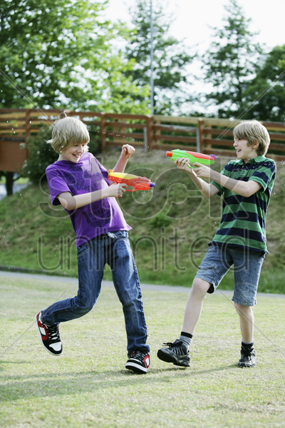 boys playing with water guns stock photo