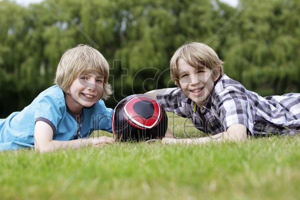 boys with soccer ball lying forward on the field stock photo