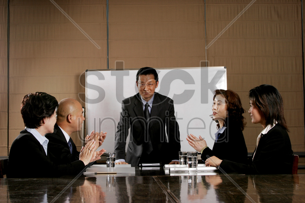 business man and women clapping their hands after a good presentation stock photo