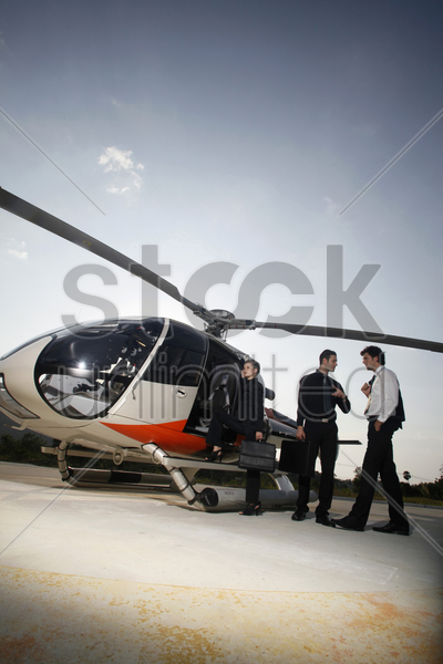 business people boarding helicopter stock photo