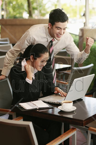 business people cheering while using laptop stock photo