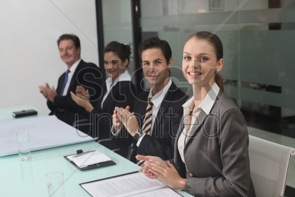 business people clapping hands in conference room stock photo