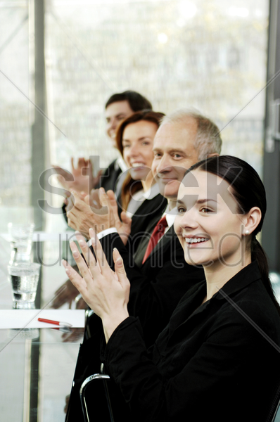 business people clapping hands while sitting in the conference room stock photo