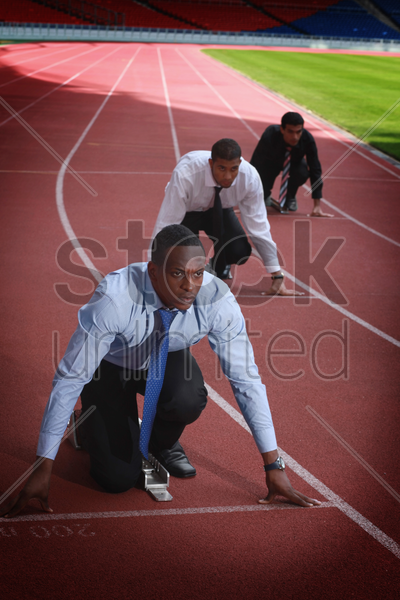 business people crouching on starting line stock photo