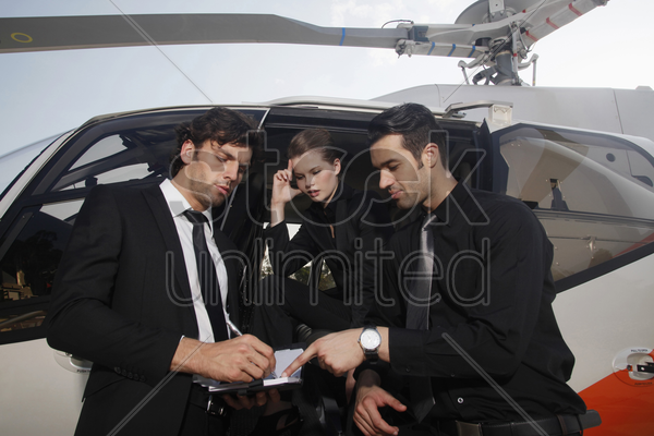 business people discussing by the helicopter stock photo