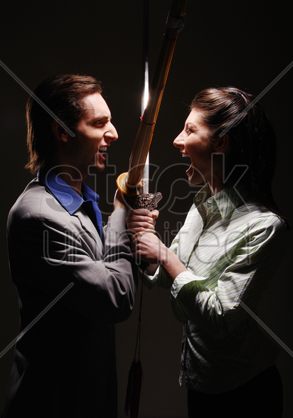 business people fighting with swords stock photo