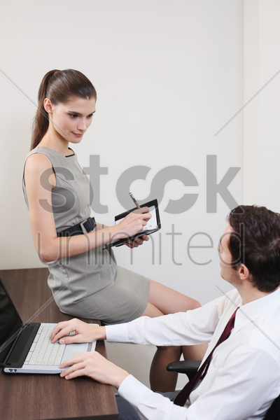 business people having discussion, businesswoman writing on organizer stock photo