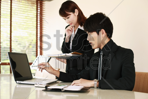 business people having discussion in front of laptop stock photo