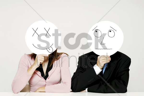 business people holding cardboard cutout with facial expression stock photo