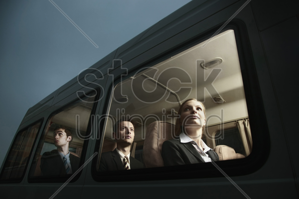 business people in a van looking out through the window stock photo
