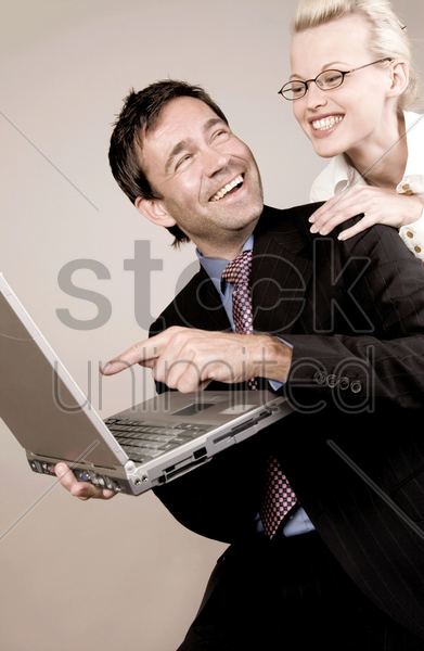 business people laughing while using laptop stock photo
