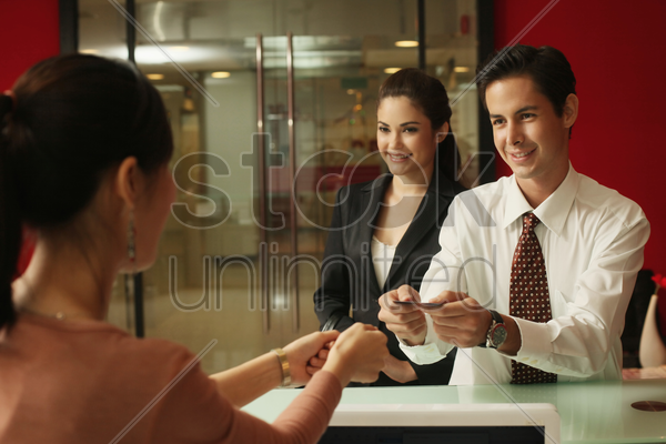 business people passing business card to receptionist stock photo