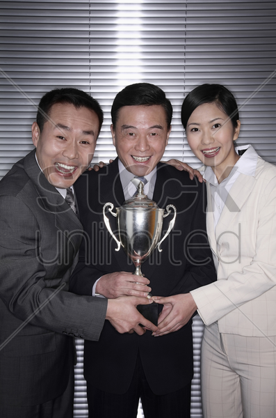 business people posing with their trophy stock photo