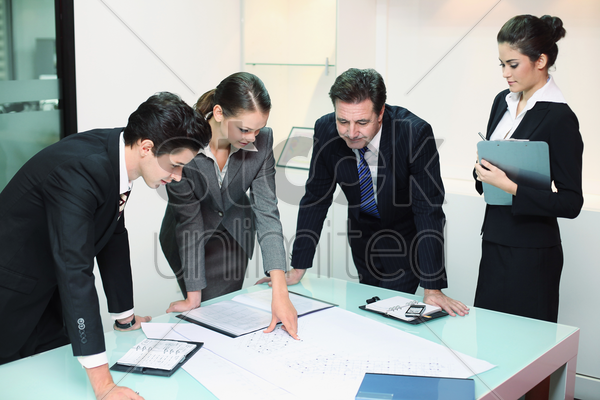 business people reviewing blueprints together stock photo